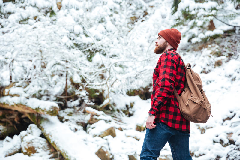 Serious bearded young man with backpack walking in winter forest royalty free stock photo
