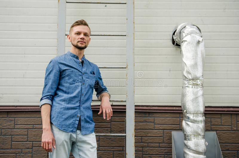Serious bearded young man in denim shirt is standing near the wall of industrial building near ladder and looking directly at the stock image