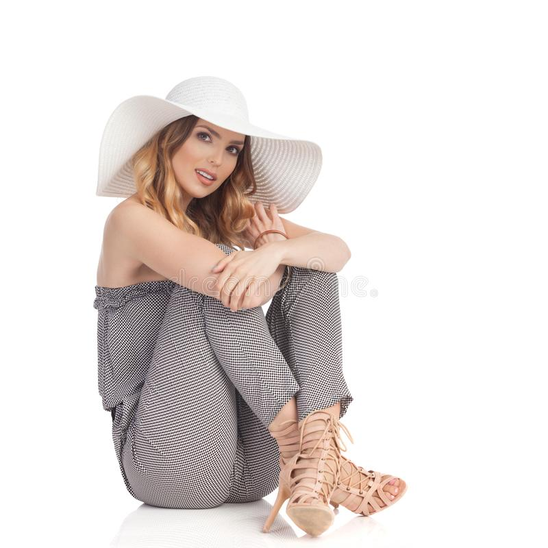 Serious Beautiful Woman In Jumpsuit, Sun Hat And High Heels Is Sitting on Floor. Serious young beautiful woman in jumpsuit, high heels and white sun hat is stock images
