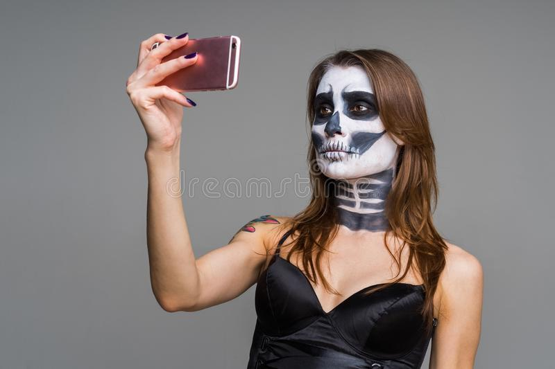 Serious beautiful young of brown-haired woman with terrifying halloween skeleton makeup using pink smart phone on a gray backgroun royalty free stock images