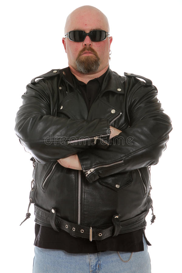 Serious biker dude. Standing arms crossed stock photo