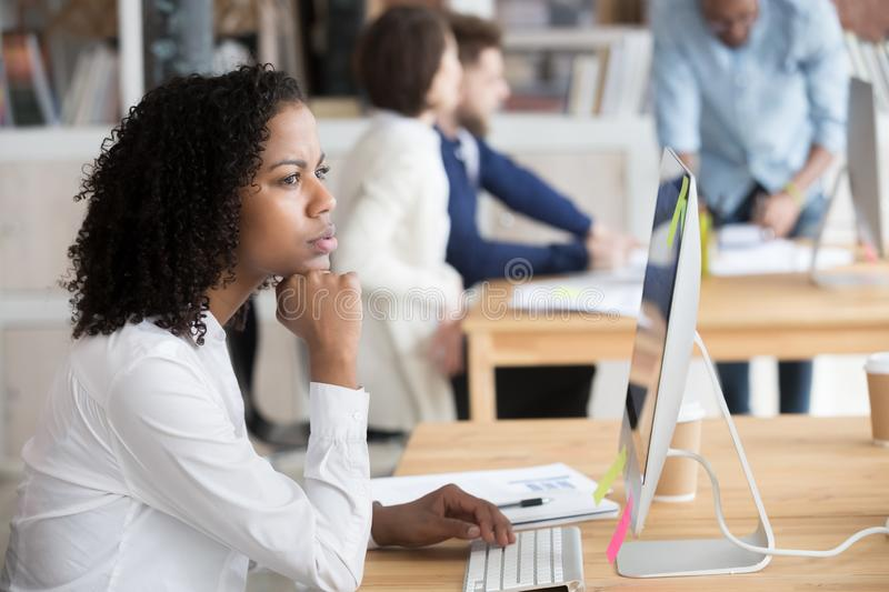 Serious black female employee thinking sitting in front of computer royalty free stock photos