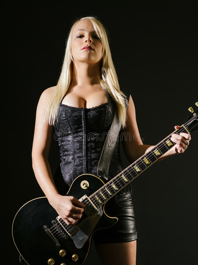 Serious blond female playing electric guitar royalty free stock images