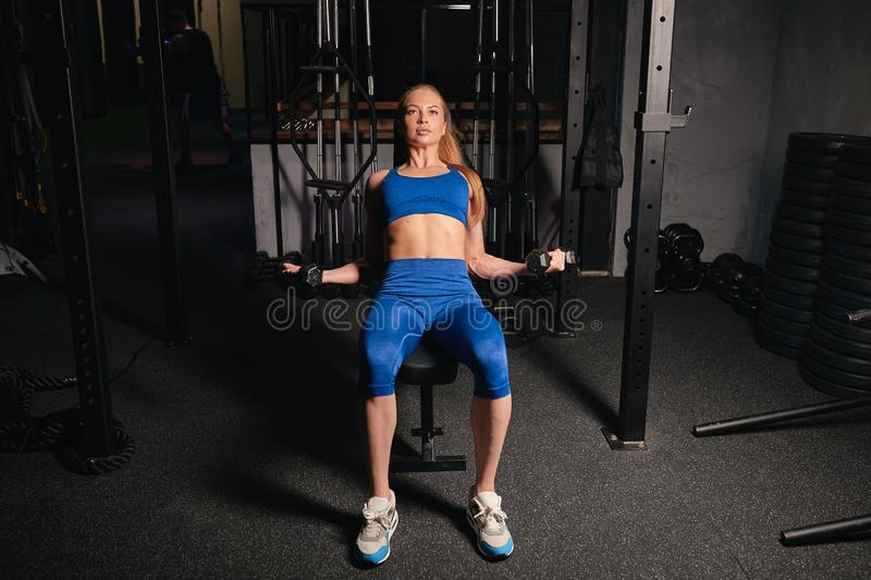 Serious blonde girl concentrated on lifting weights stock images