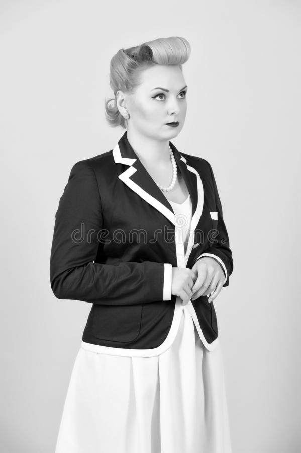 Serious blonde girl in jacket looks up. Woman in pin-up style dressed in jacket on grey stock photo