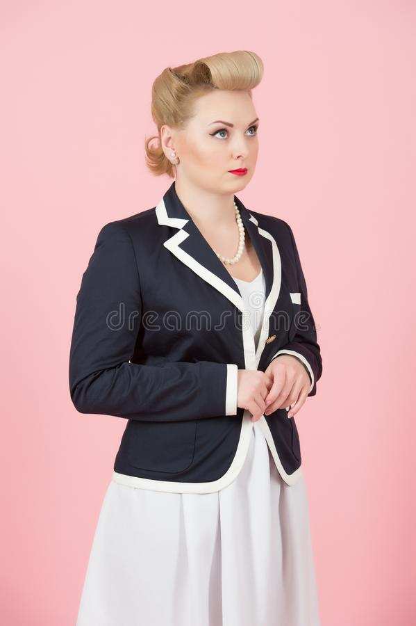 A Serious blonde girl in jacket looks up. Woman in pin-up style dreaming standing in studio with closed hands. royalty free stock photo