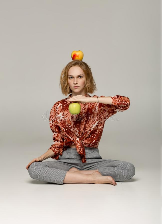 Serious blonde girl in trendy red shirt sitting in yoga position stock photos
