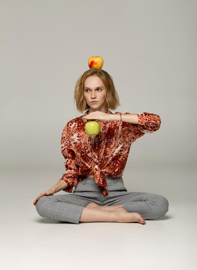 Serious blonde girl in trendy red shirt sitting in yoga position stock images