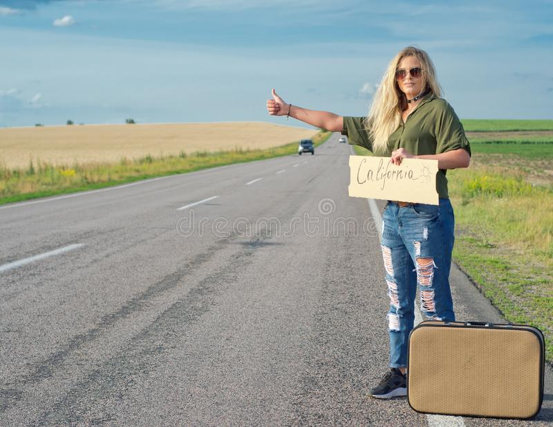 Beautiful girl hitchhiking on the road traveling. Serious blonde holding sign while hitchhiking on the road in summertime royalty free stock images