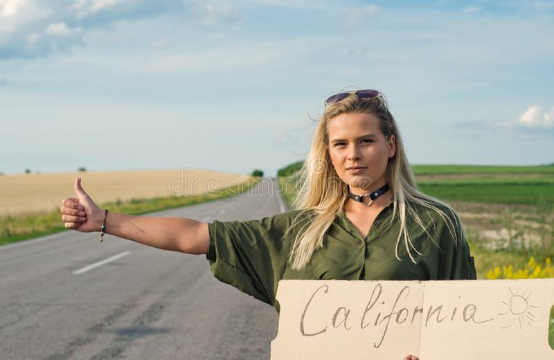 Beautiful girl hitchhiking on the road traveling. Serious blonde holding sign while hitchhiking on the road in summertime stock images