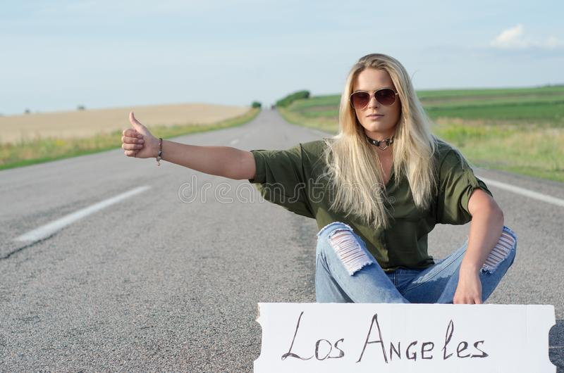 Beautiful girl hitchhiking on the road traveling. Serious blonde holding sign while hitchhiking on the road in summertime royalty free stock image