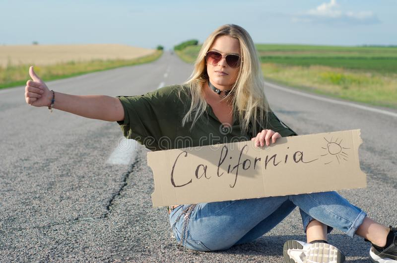 Beautiful girl hitchhiking on the road traveling. Serious blonde holding sign while hitchhiking on the road in summertime stock photography