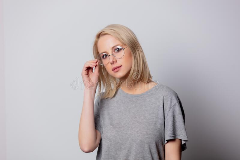 Serious blonde woman in glasses on white background royalty free stock photography