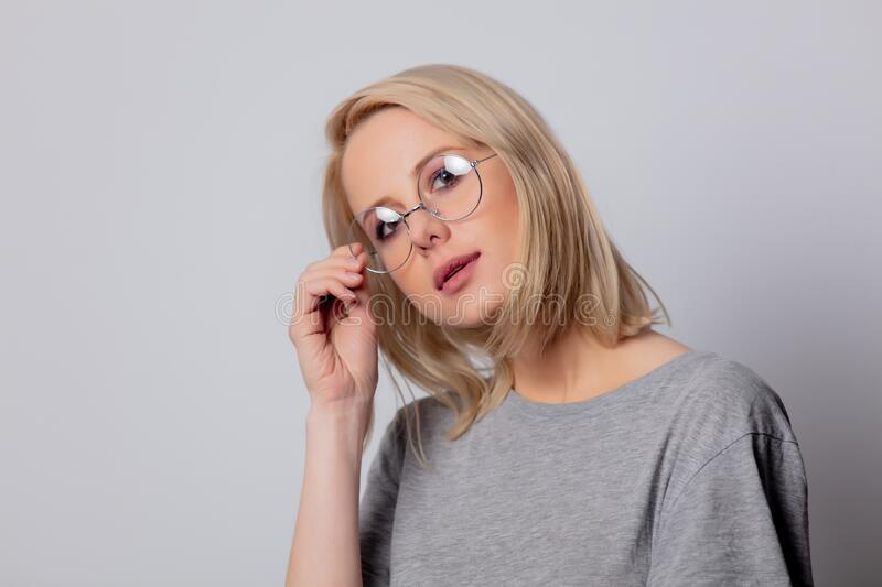 Serious blonde woman in glasses on white background stock photo