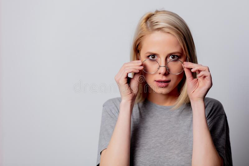 Serious blonde woman in glasses on white background stock image