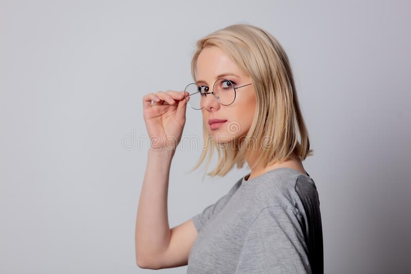 Serious blonde woman in glasses on white background stock images