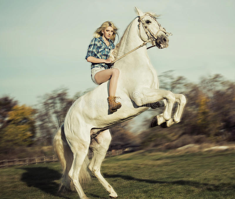 Serious blonde woman riding the horse stock image