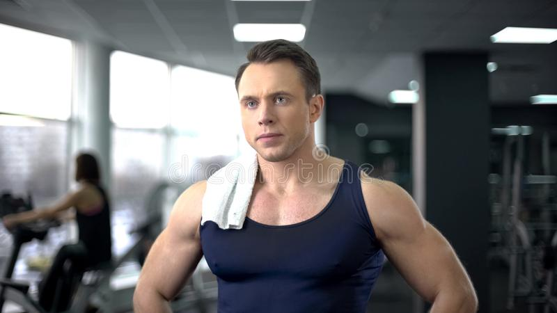 Serious bodybuilder with towel on shoulder relaxing after hard workout in gym stock image