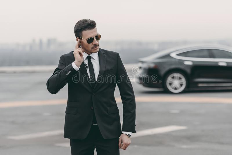 serious bodyguard listening message with security earpiece stock photography