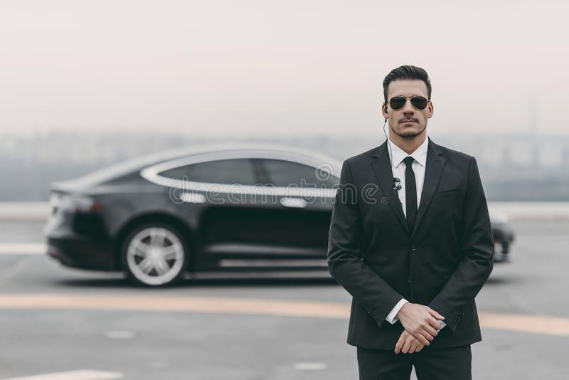 serious bodyguard standing with sunglasses and security earpiece royalty free stock image