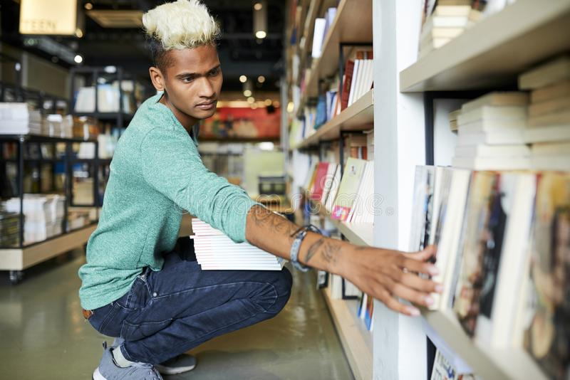 Serious bookstore worker reshelving books. Serious handsome black bookstore worker with blond Mohawk and tattoos on arm crouching on floor and reshelving books stock photo