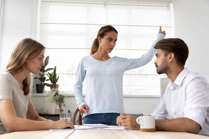 Serious boss scolding employees for bad work results at briefing royalty free stock photo