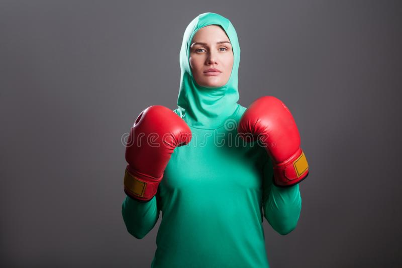 Serious boxing athlete muslim woman in green hijab or islamic sp royalty free stock photo