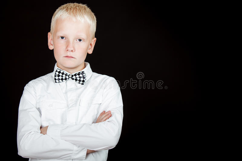 Serious boy with arms crossed wearing bow tie. And white shirt stares at camera royalty free stock photos