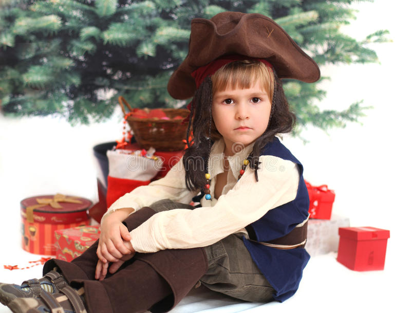 The serious boy in cocked hat. Under xmas tree stock image