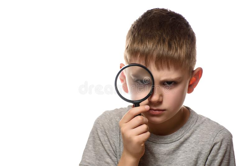 Serious boy with a magnifying glass in his hands. Little explorer. White background.  royalty free stock images