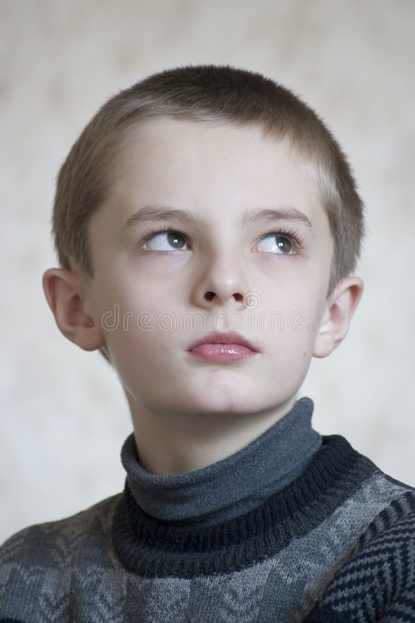 Serious boy portrait. On neutral background royalty free stock photography