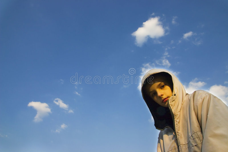 Serious boy portrait. On blue sky background stock photography