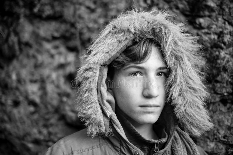 Serious boy portrait with winter clothings - black and white photo royalty free stock image