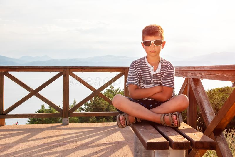 A serious boy is sitting on the bench against the backdrop of a beautiful sea landscape stock photography