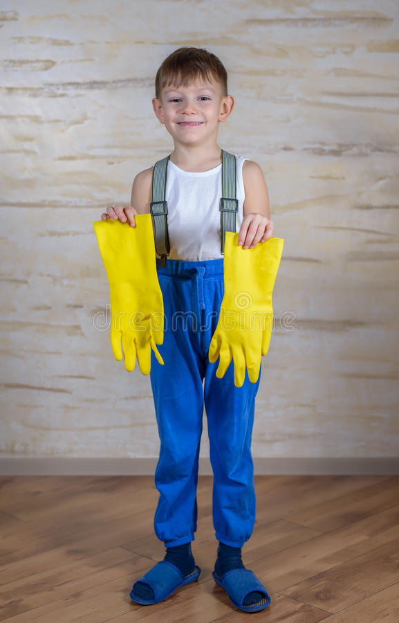 Serious boy in slippers putting on gloves royalty free stock photo