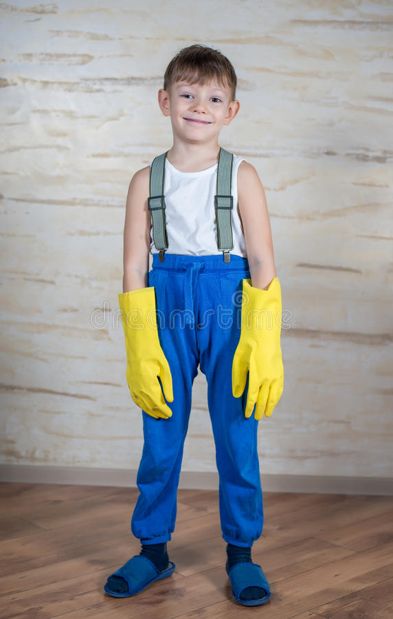 Serious boy in slippers putting on gloves stock photos