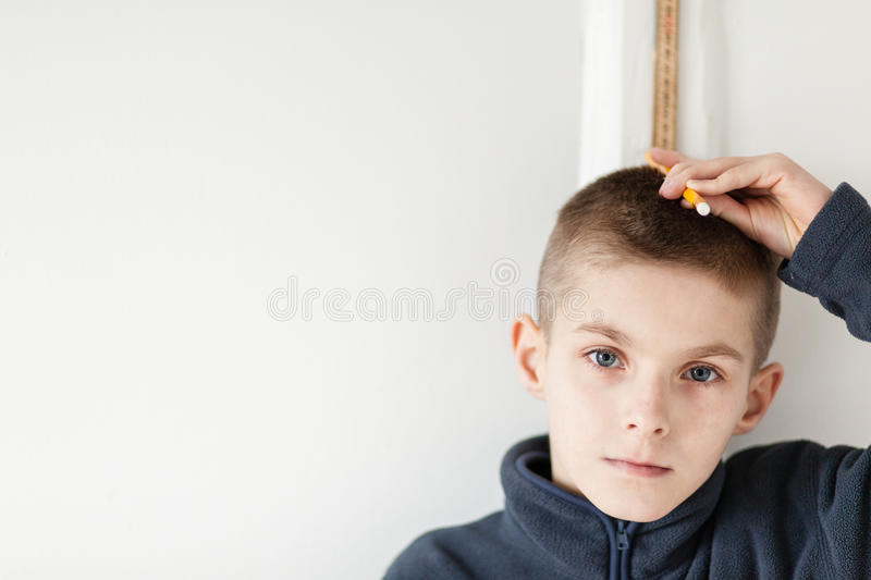 Serious Boy Standing on the Wall to Check Height royalty free stock image