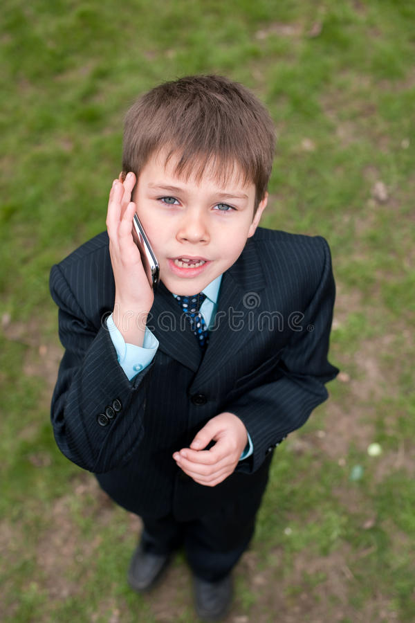Serious boy in suit speaking over the mobile royalty free stock photos