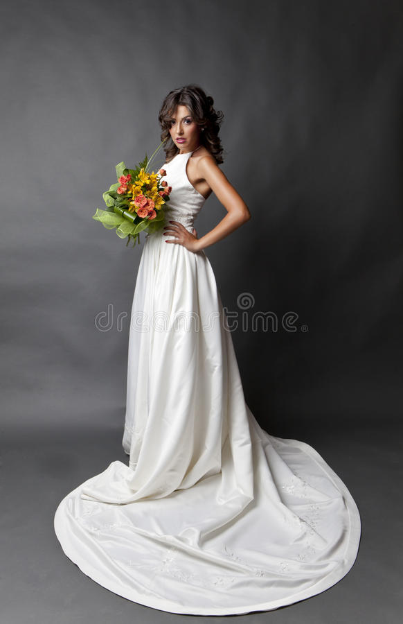 Serious bride. Young serious bride with white wedding dress and wedding bouquet posing on studio background royalty free stock images