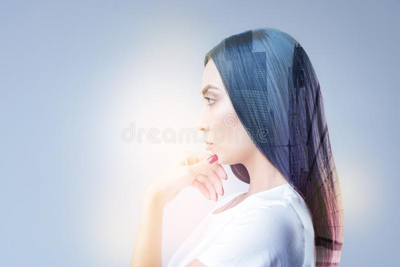 Serious brunette girl standing in semi position. Thinking about him. Concentrated female person pressing lips and raising eyebrows while looking forward stock photo