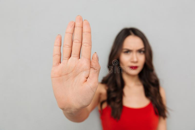 Serious brunette woman in casual clothes showing stop gesture stock photography