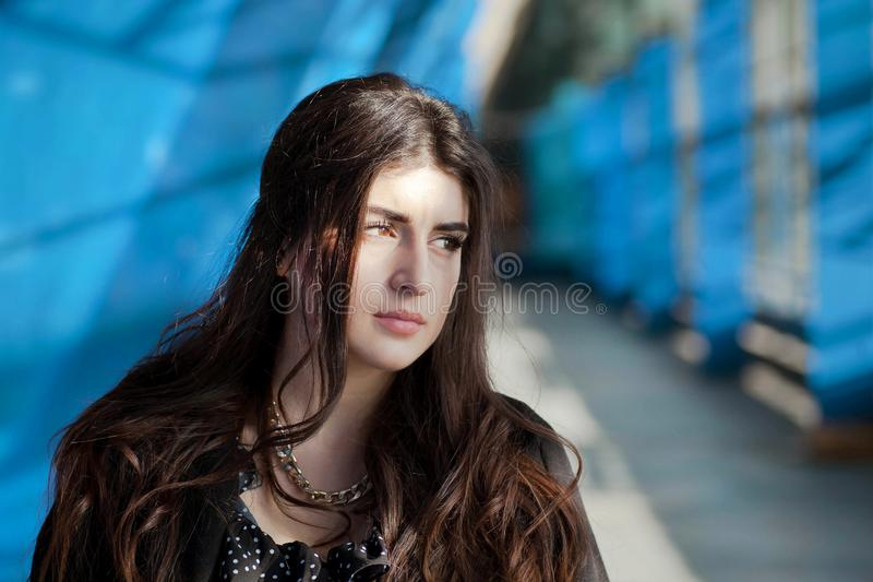 Serious brunette woman standing under blue color walls of rustic city area. Young girl thinking in urban city exterior. S royalty free stock images