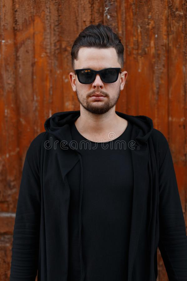 Serious brutal handsome young male hipster with fashionable hairstyle with beard in stylish sunglasses in modern black clothes royalty free stock photography