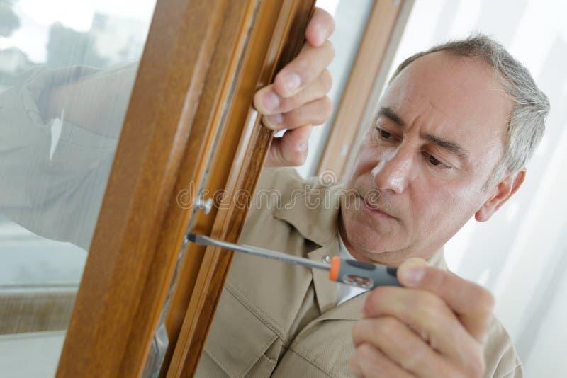 Serious builder installing window. Serious builder installing a window royalty free stock photography