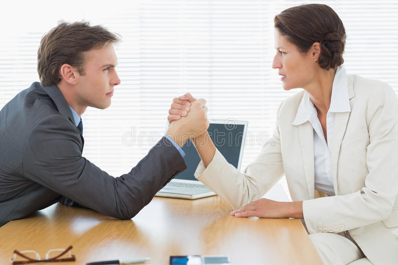 Serious business couple arm wrestling at office desk. Side view of serious young business couple arm wrestling at office desk royalty free stock image