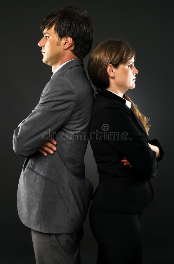 Serious business couple standing back to back royalty free stock image