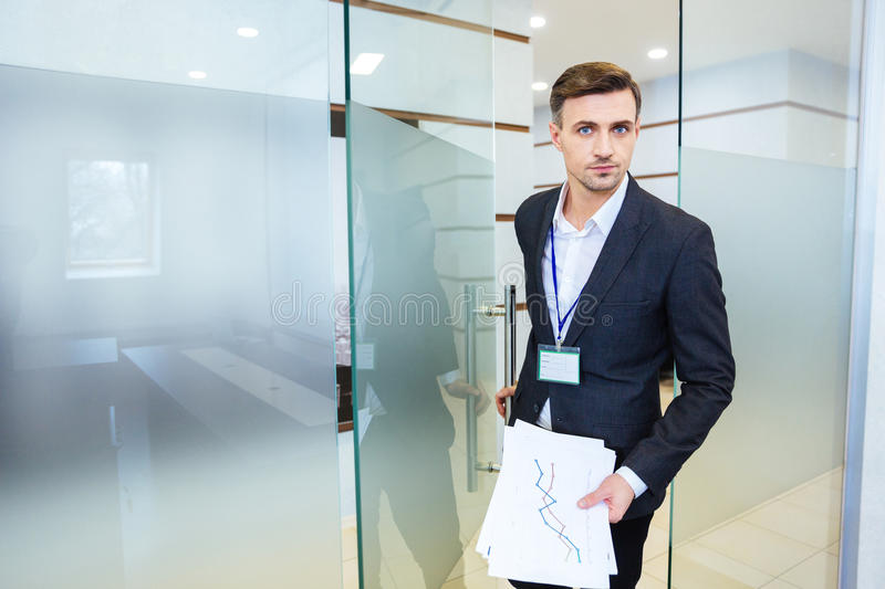 Serious business man entering the meeting room. Serious handsome business man holding financial report and entering the meeting room royalty free stock photo