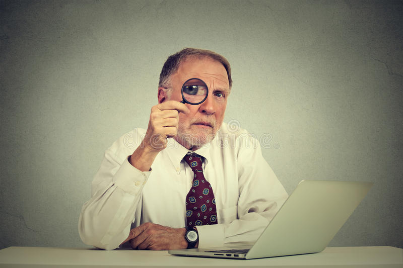Serious business man in glasses skeptically looking through magnifying glass. At you sitting at office table with laptop computer isolated gray background royalty free stock photos