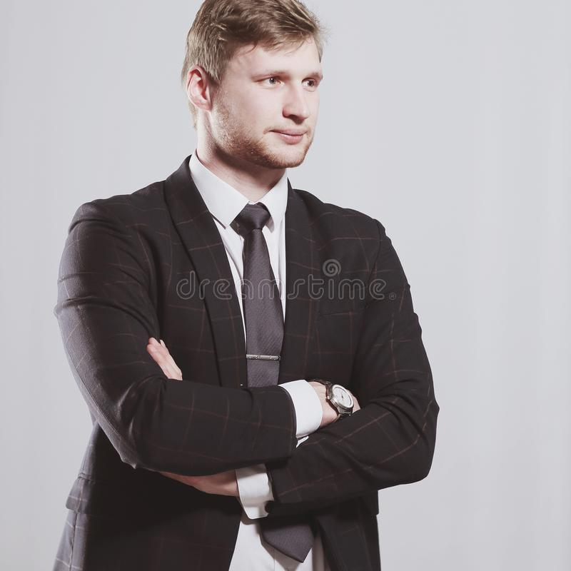 Serious business man stands with his arms folded.isolated stock photography