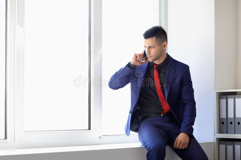 Serious business man talking on cell phone sitting on window sill royalty free stock photo
